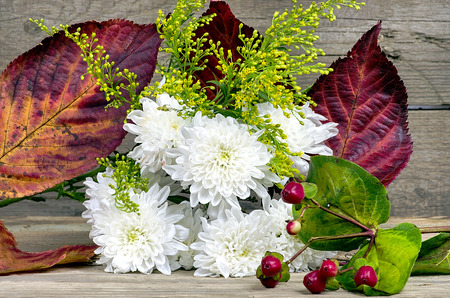 White chrysanthemum on a wooden table with wooden background photo