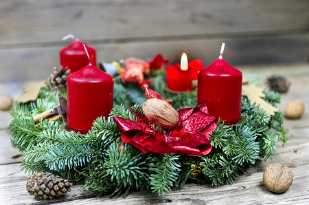 Advent wreath with burning candle on the wooden background photo