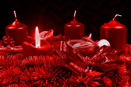 Red Advent wreath with burning candles on black background photo