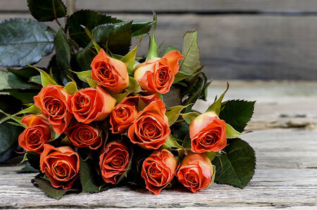 Bouquet of yellow-red roses on an old wooden table photo