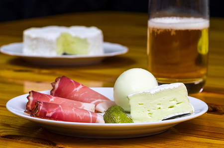 Plate with ham cheese cucumber egg and a glass of beer on a wooden table photo