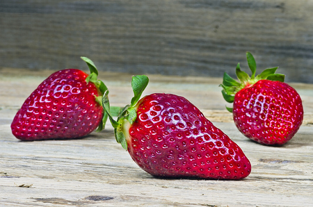 Three strawberries on an old wooden table photo