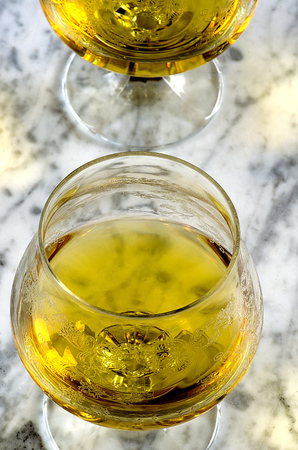 cognac: Glass of cognac on a marble table brown gray