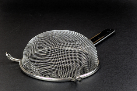 sieve: Kitchen sieve on a black background, decoration