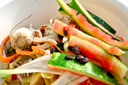 Vegetable scraps in a white plastic bowl bio waste, carrots, cesium, watermelon, potato peels, leek Stock Photo