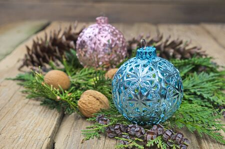 pinecones: Blue and pink Christmas balls on green pine needles with walnuts and pinecones on wooden table decoration