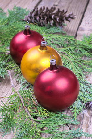 pine three: Three colored Christmas balls on pine needles on a wooden table in the background with pinecones