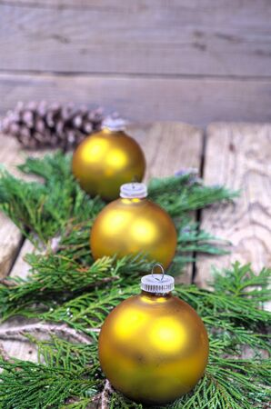 pine three: Three yellow Christmas balls on green pine needles on a wooden table decorations