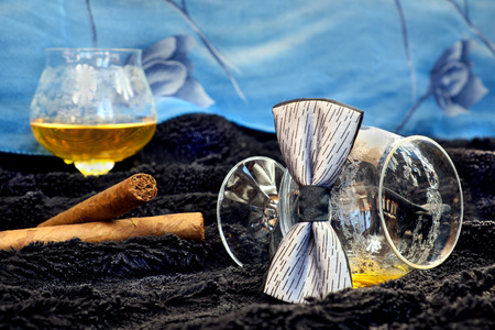 drunks: Glass of cognac with a cigar on a black velvet with a blue backdrop, alcohol, decorations, still life