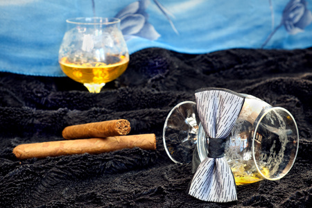 drunks: Glass of cognac with a cigar, bow tie on a black velvet with a blue backdrop, alcohol, decorations, still life