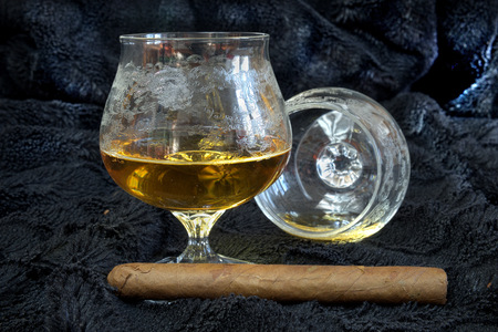 drunks: Glass of cognac with a cigar on a black velvet, alcohol, decorations, still life Stock Photo