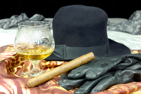 brown leather hat: Black hat on a brown scarf with black leather gloves and a cigar on a marble table, fashion accessories, fashion