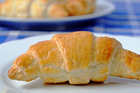 placemats: Homemade croissant on a white plate on a blue checkered placemats, breakfast Stock Photo