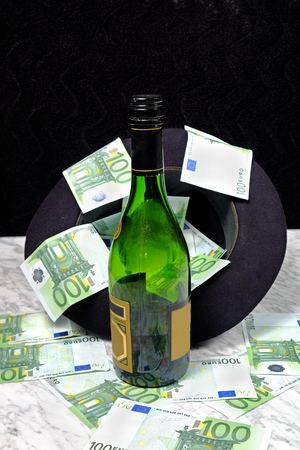 one hundred euro banknote: One hundred euro banknotes with a black hat bottle of cognac on the marble table on a black background