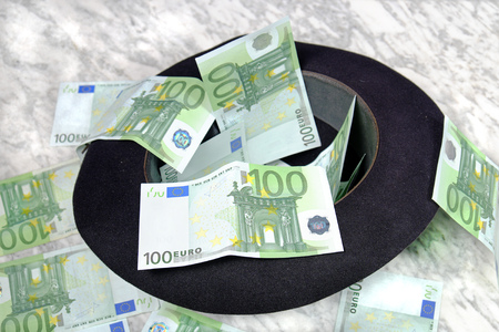 one hundred euro banknote: One hundred euro banknotes with a black hat on a marble table on a black background Stock Photo