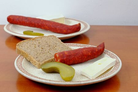 salame: Sausages with a slice of bread, cheese and pickle on a plate on the wooden table