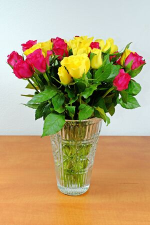 glass vase: Bouquet of yellow and pink roses in a glass vase on a wooden table