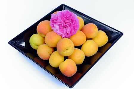 fruit plate: Ripe apricots on a black plate with rose on a white background isolated, fruit, diet, health Stock Photo