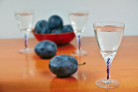 spirituous beverages: Glasses of homemade plum brandy with plums on wooden table on a white background