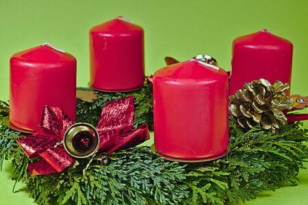 corona de adviento: Corona de Adviento con velas rojas sobre un fondo verde Foto de archivo