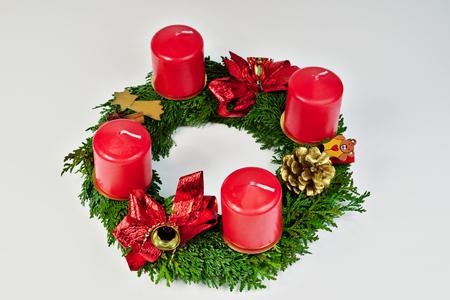 corona de adviento: Corona de Adviento con velas rojas sobre un fondo blanco aislado