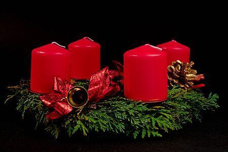 corona de adviento: Corona de Adviento con velas rojas sobre un fondo negro