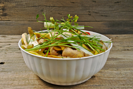 Organic kitchen waste in a white plastic bowl on wooden table
