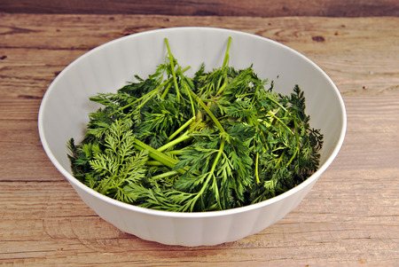 kitchen scraps: Bio waste-carrot tops in a white plastic bowl on old wooden table