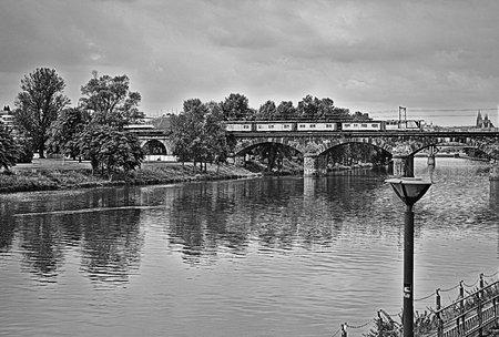 A train crossing a bridge over a river in black and white
