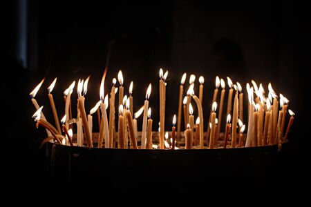Prayer Candles in a Church on dark background Stock Photo