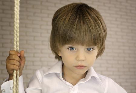 Blauwogige jongen in een wit overhemd met touw