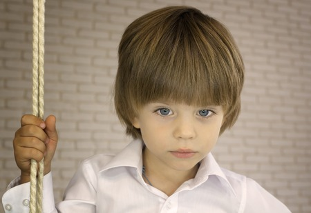 Blue-eyed boy in a white shirt with rope