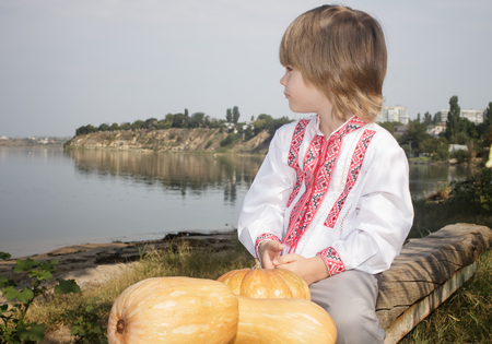 Autumn portrait of a little boy in a white embroidered shirt