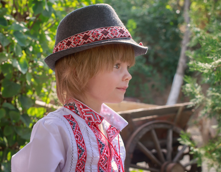 Portrait of a little boy in a white embroidered shirt and a hat