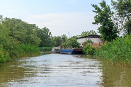 Danube river and view of the small house and barge on a summer day. Vilkovo, Ukraine