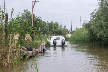 Vilkovo, Ukraine - May, 26, 2018: Canal along the street, reeds and white motor boat Editoriali