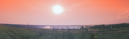 Panoramic view of the field of solar panels. The sun rose above the horizon, the rays falling on the solar panels and plants.