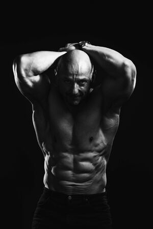 Black and white portrait of bald shirtless male bodybuilder with perfect six pack prompting to sport and training. Foto de archivo