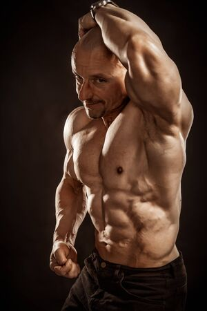 Fitness portrait of bald shirtless male bodybuilder with perfect six pack prompting to sport and training.