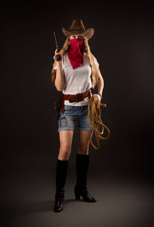 Portrait of a girl in a cowboy hat, with a red bandana on her face, with a gun in her hand Foto de archivo