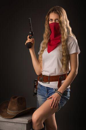 Retrato de una niña con un sombrero de vaquero, pañuelo y una pistola Foto de archivo