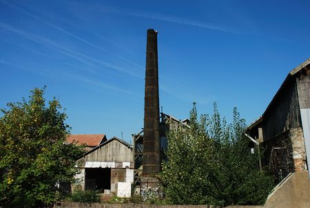 Outdoor view of an abandoned factory, showing a broken brick smokestack