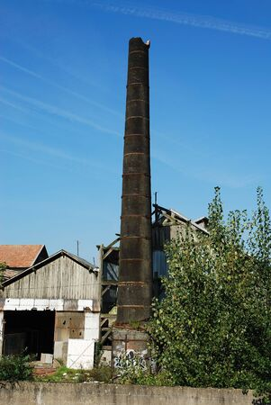 Outdoor view of an abandoned factory, showing a broken brick smokestack. Vertical view. Stock Photo