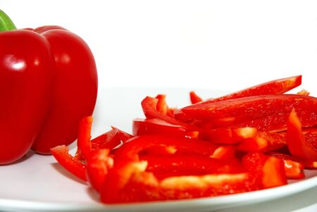 Red bell pepper and slices, isolated on white background.