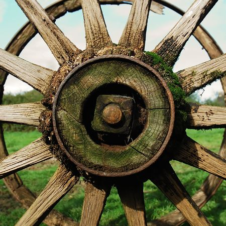 Partial view of an old rusty wagon wheel, with grass and sky backgrounds