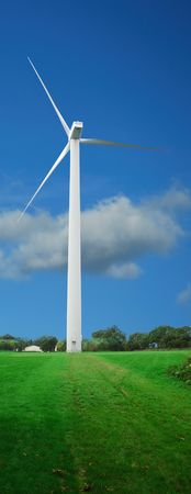 Vertical view of a wind turbine on a green field. Cloudy sky background. (includes turbine path)