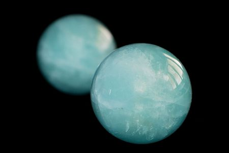 Two emerald green zen stress balls, isolated over a black background. Originated from China, these balls are to be rolled around in the palm of one hand. Stock Photo