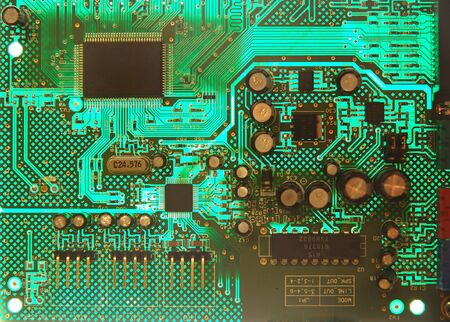 dominant color: Close view of backlit printed circuit board (PCB) with components. Green dominant color. Black space on upper left chip for possible added text.