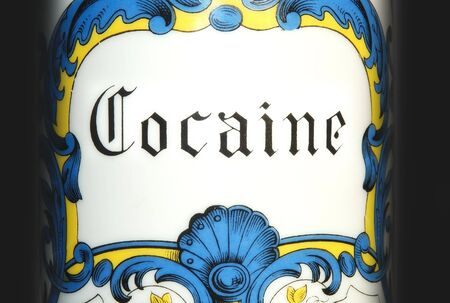 Detailed shot of an antique cocaine jar on black background. Stock Photo