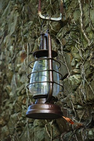 Old kerosene lamp hanged on a sandstone wall